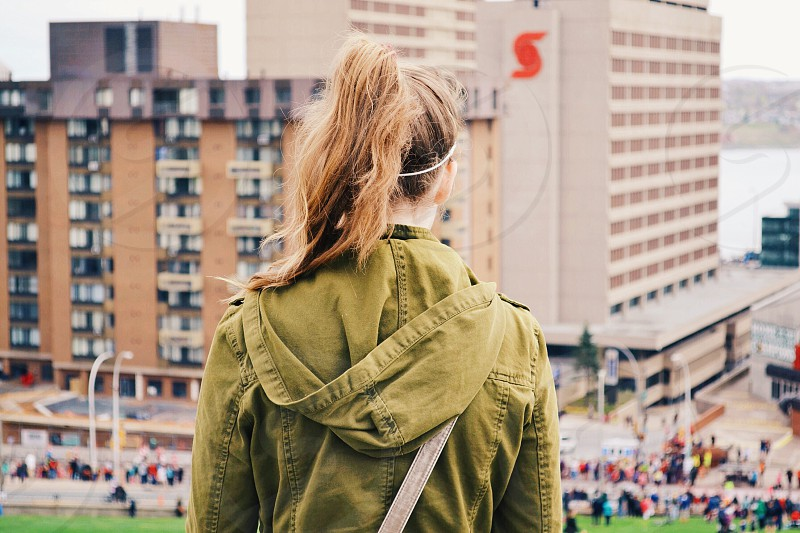 woman in army green hooded jacket looking out over town photo