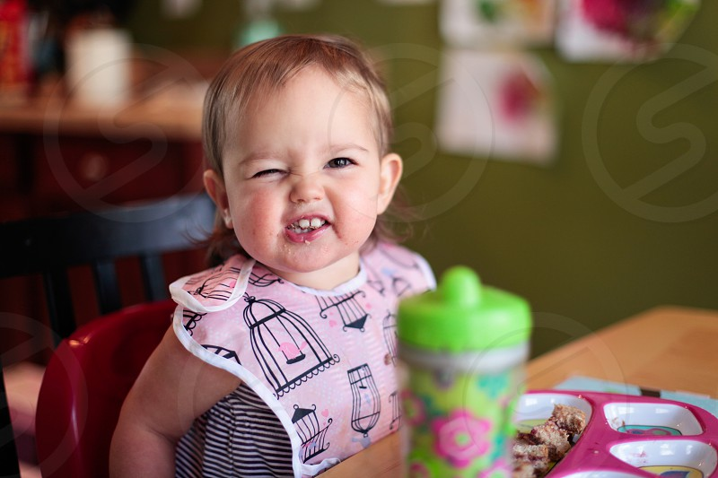 baby wearing pink and black bin and black and white pinstripe sleeveless shirt on red high chair beside brown wooden desk with green plastic bottle near green painted wall photo