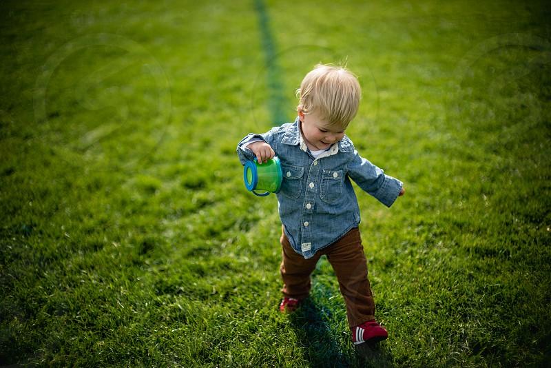 boy in blue denim dress shirt walking photo
