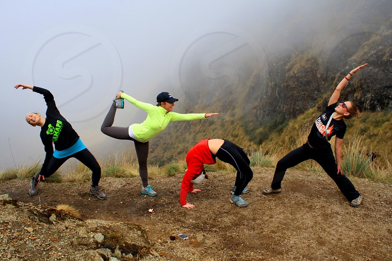 group of people wearing hiking apparels bending near mountain covered with fogs photo