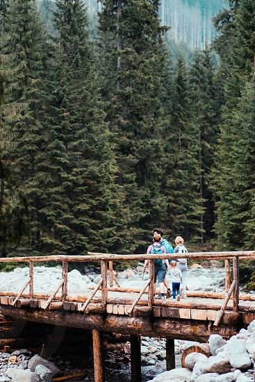 Family walking across a wooden bridge over a mountain stream. Spending vacation on wandering with backpacks in a mountains and forests photo