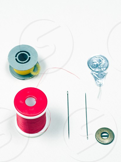 thread needle paperclips red green yellow robin button  photo