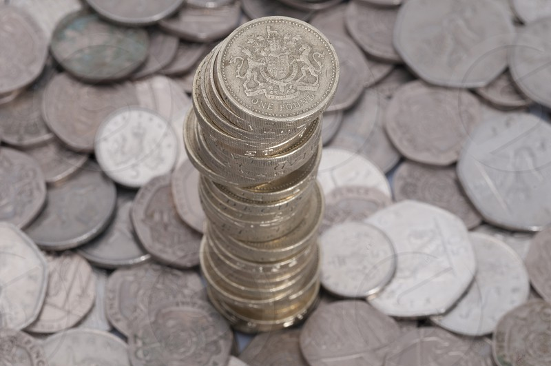 A stack of Pound coins rising up out of various other coins. photo