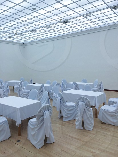 Tables and chairs covered in white in empty room photo