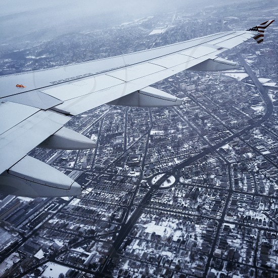 white airplane wing over high rise buildings during daytime photo