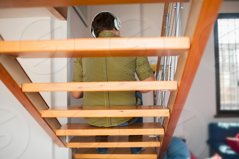 Back view of a man sitting on wooden stairs and enjoying favorite music in wireless headphones. Leisure time and relaxing at home photo