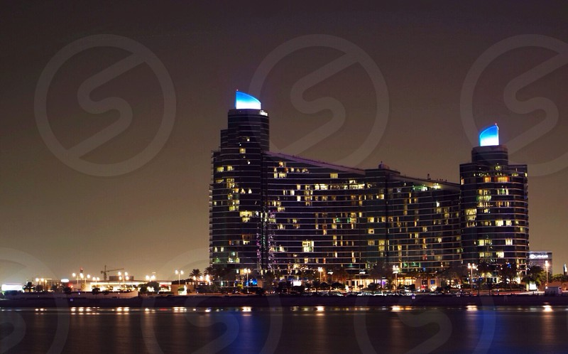 tall large building with lots of lights at night on water photo
