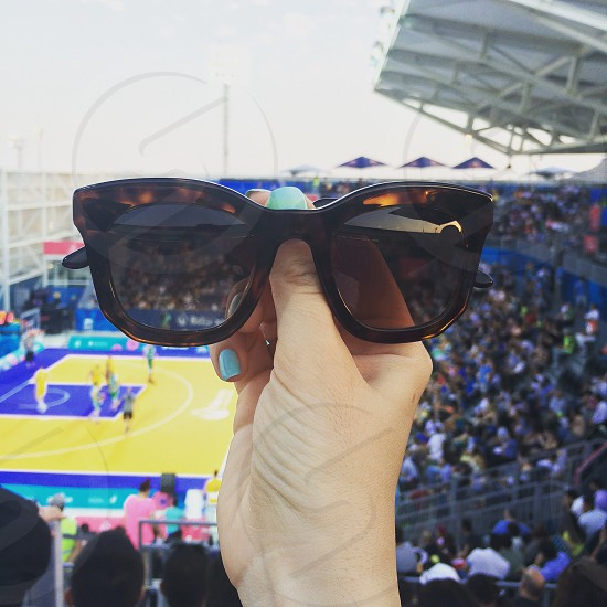 person holding brown oversize sunglassesd photo