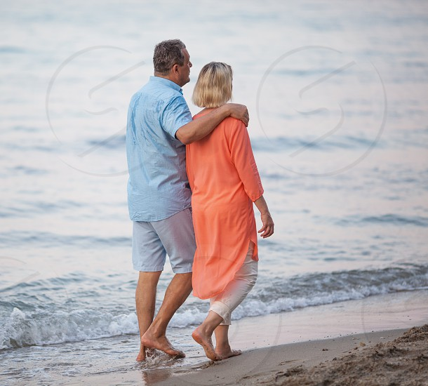 Senior couple walking together along the coast. Man embracing the woman while they having enjoyable barefoot outing on the beach photo