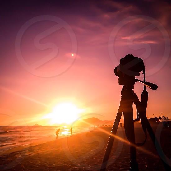 black dslr camera with tripod on beach photo