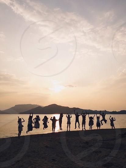 people jump on seashore photo