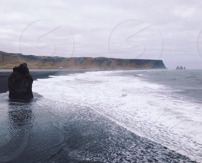 View of the ocean and black sand beaches from a cliff in Iceland.  photo