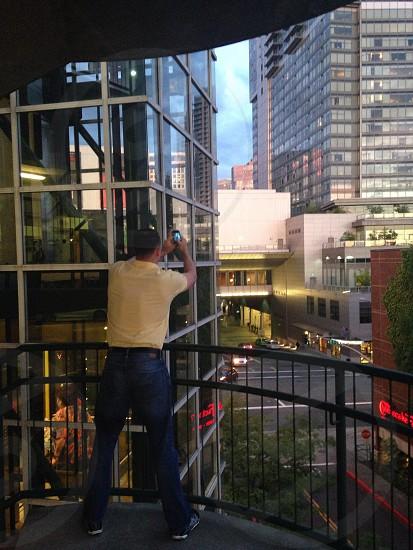 man standing holding smartphone photo