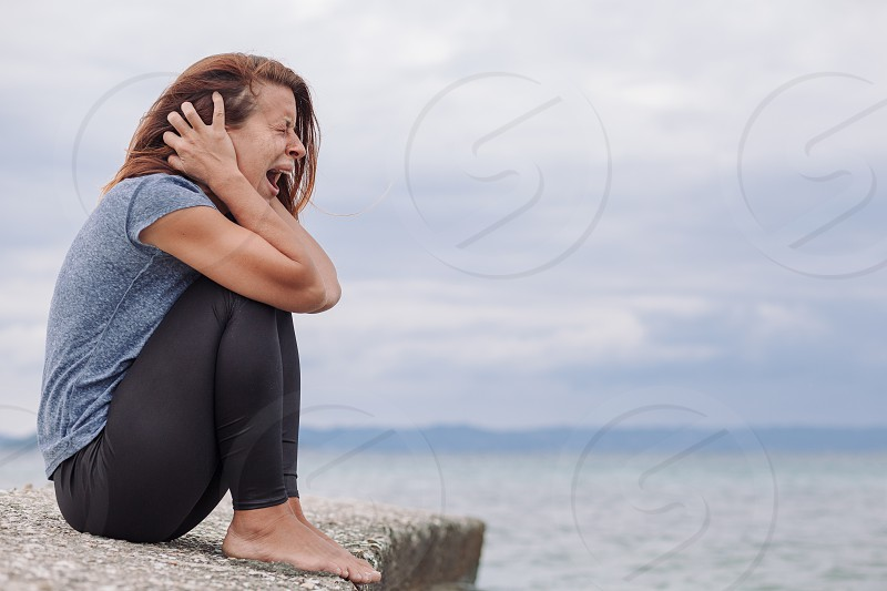Woman alone and depressed screaming on the bridge photo