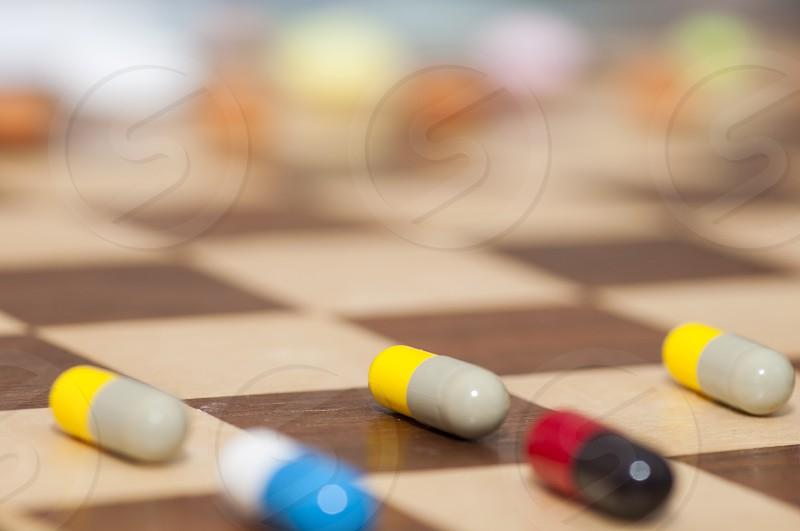 Various pills on chessboard photo