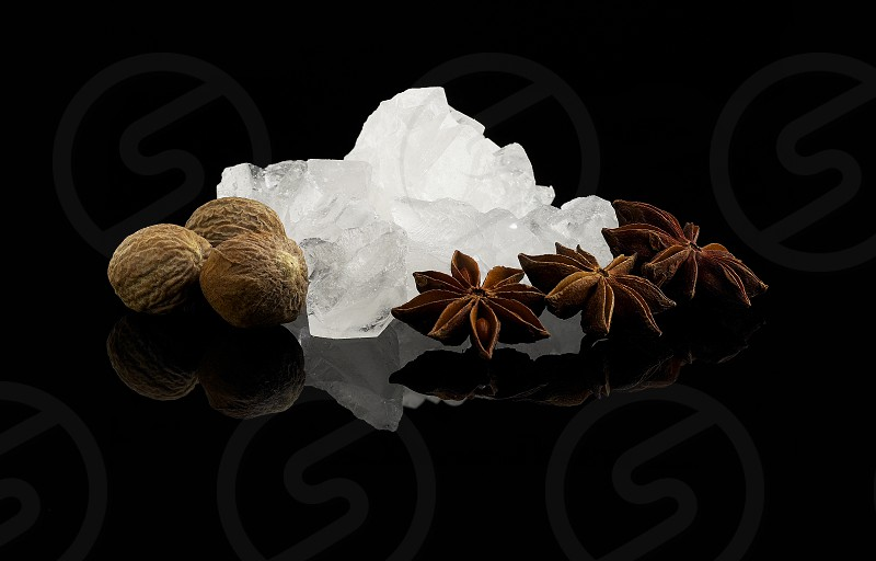 crystal sugar and spice  over black reflective surface background photo