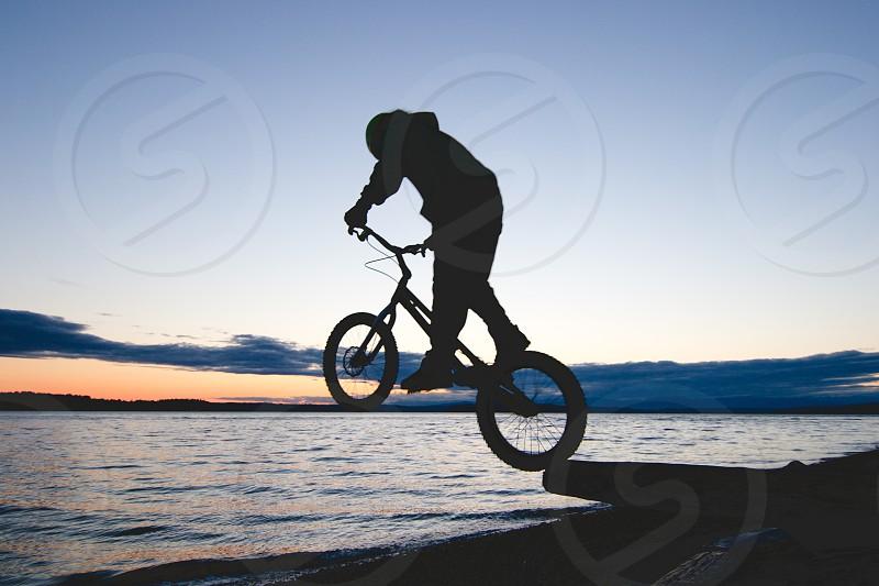 silhouette of a person biking near the beach photo