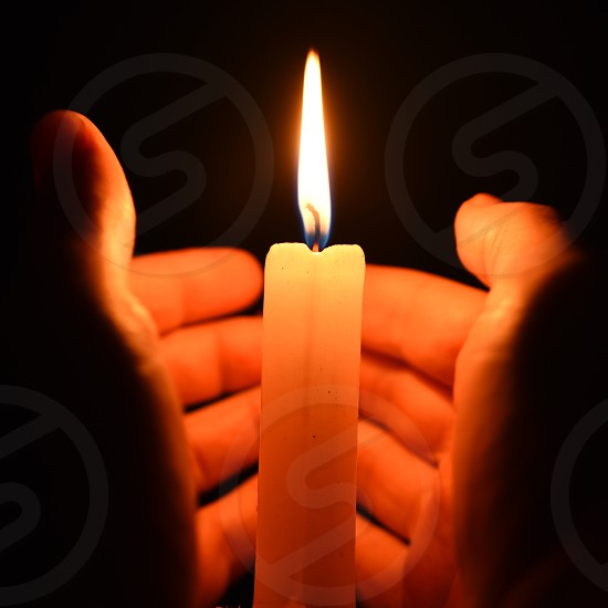 person trying to cover enlighten candle stick photo