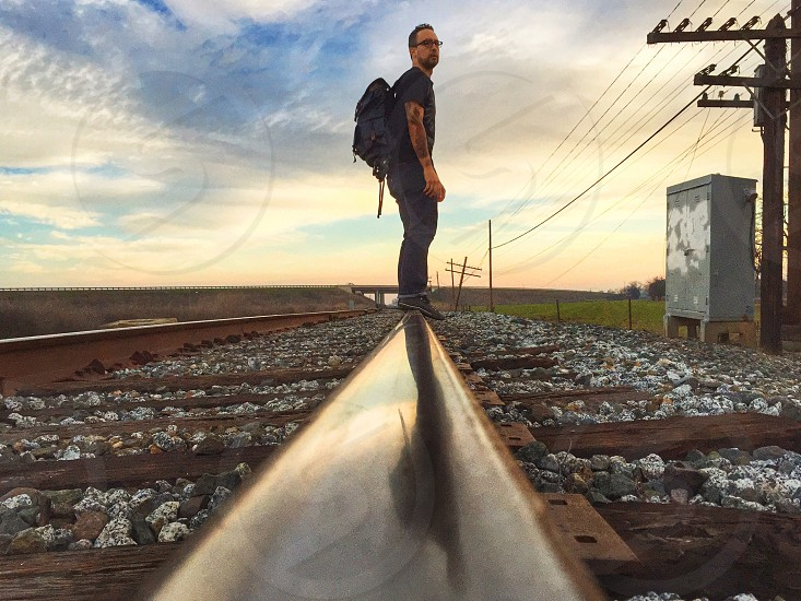 man in black with black backpack standing on train track photo