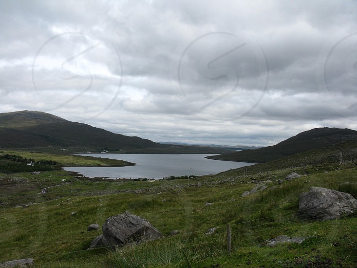 gray white cloudy sky above  gray lake bordered by low dark green hills photo