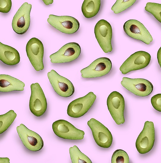 halves of a green avocado on a pink background flat lay photo