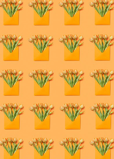 Yellow tulip bouquets in handcraft envelopes pattern on an orange background. Post card for congratulation. Flat lay. photo