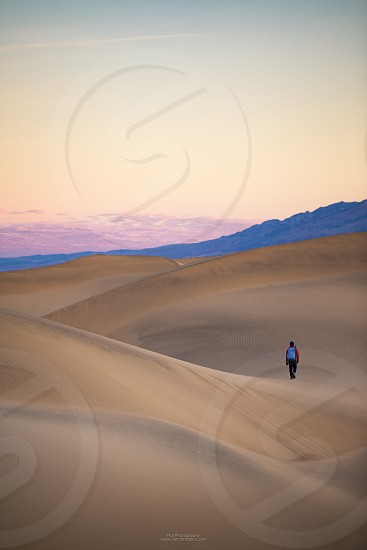 This is picture of a male hiker hiking at Mesquite Flat Sand Dunes during sunset at Death Valley National Park California. photo