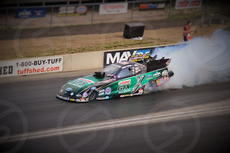 green and black Castrol race car burnout on road photo