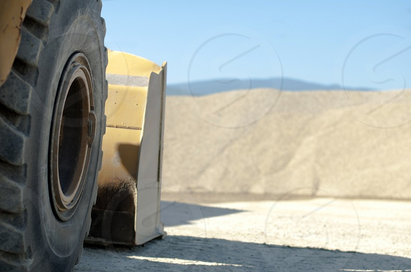 Tire backhoe close-up and piles of sand background photo
