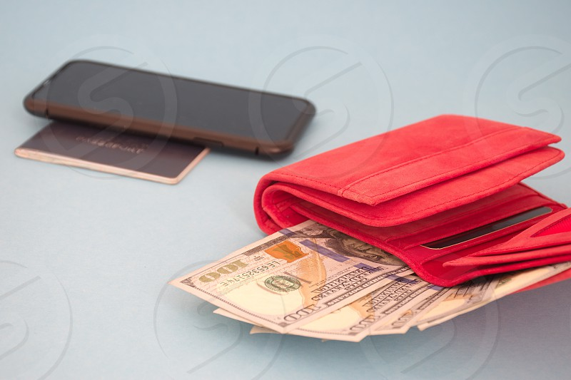 Red wallet with dollar banknotes mobile phone and passport against the blue background photo
