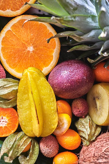 Fresh juicy tropical fruits as a backgraund. Passion fruit carambola litchi kumquat orange halves phisalis on a green leaves. Close-up. Top view. Concept of healthy dieting food. photo