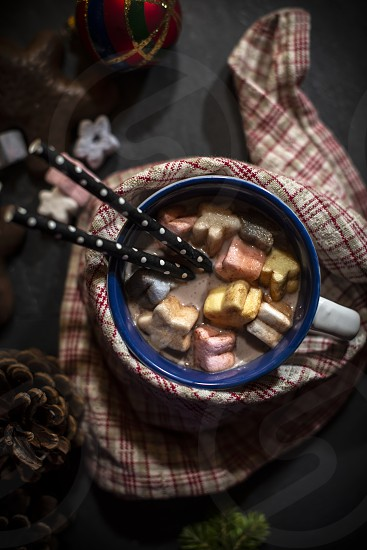 Cup of milk and Marshmallow. Christmas lights and ornaments photo
