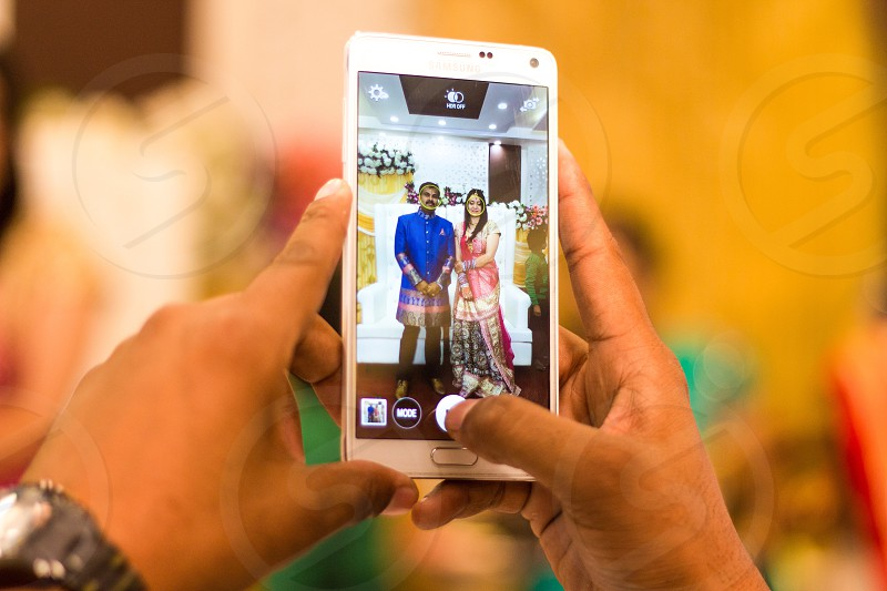 person taking a photo of man wearing kurta and woman in saree photo