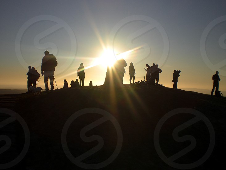 Hikers bikers dog walkers silhouetted against evening sun on Mam Tor Peak District England photo