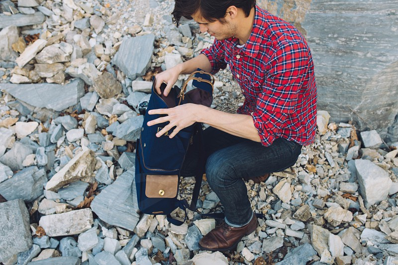 man wearing red and blue checked button up sports shirt and blue denim jeans sitting in grey rock opening his blue backpack photo