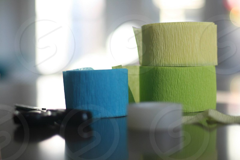 yellow green and blue crepe paper spool beside black handled scissors photo