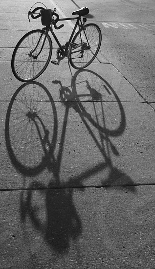 bicycle shadow silhouette exercise equipment transportation black and white object photo