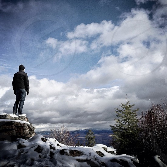 man standing on snowy rock photography photo
