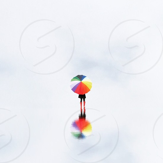 woman in red rain boots carrying red white orange blue green and yellow umbrella photo