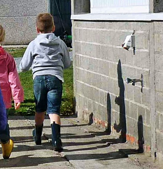 boy wearing a grey hoodie and rainboots walking in front of other children photo