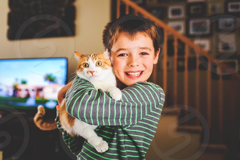 young boy poses with cat indoors photo