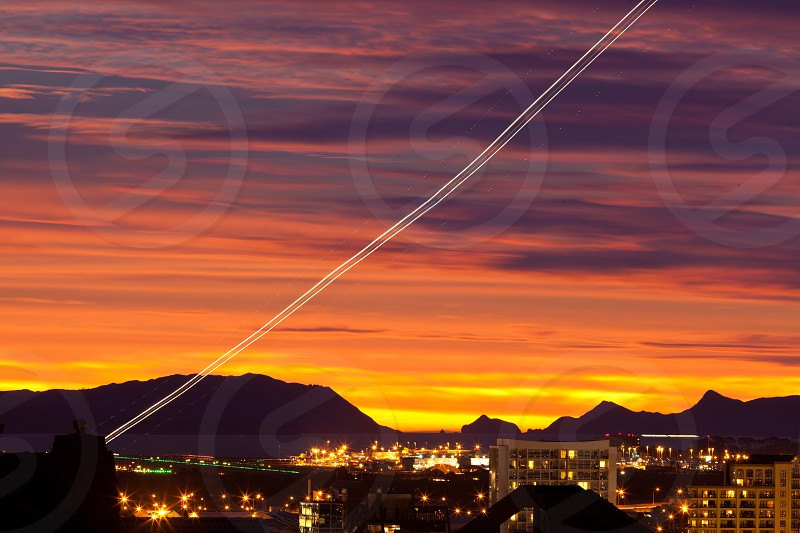 Sunset and light trail of starting airplane over Manukau  southern suburb of Auckland  New Zealand photo