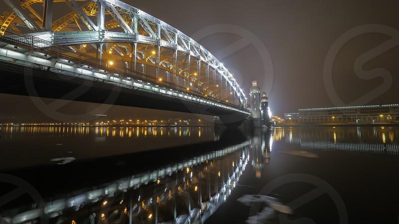 Illuminated Peter the Great Bridge across Neva River in night Saint Petersburg Russia photo