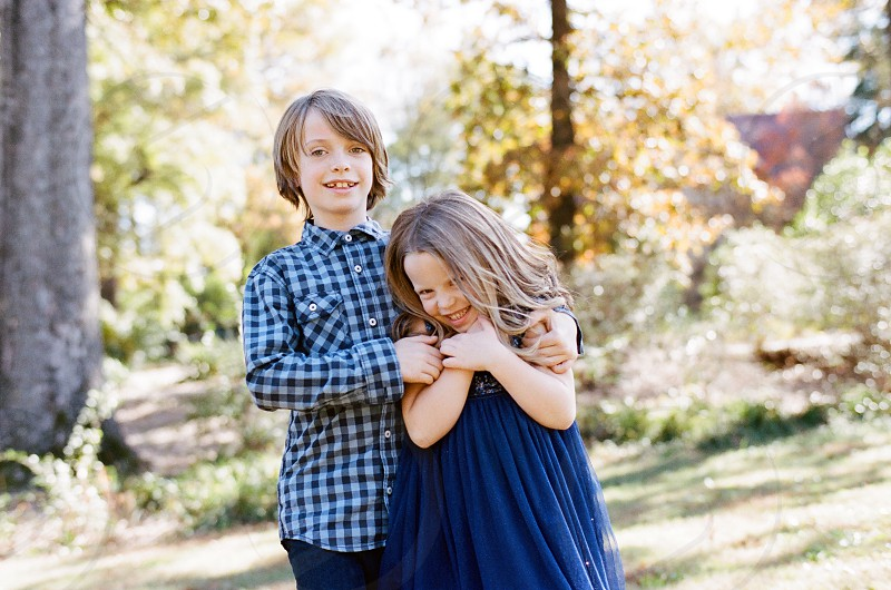 siblings brother sister family holiday photo outside park  daytime natural lighting photo