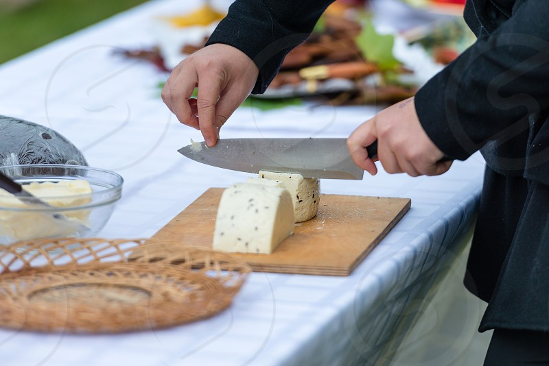 Worker slicing the cheese. Close up of  hands cut with a knife cheese - Image photo