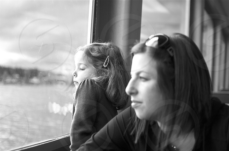 Mother Daughter staring out window of a ferry boat - Seattle WA photo