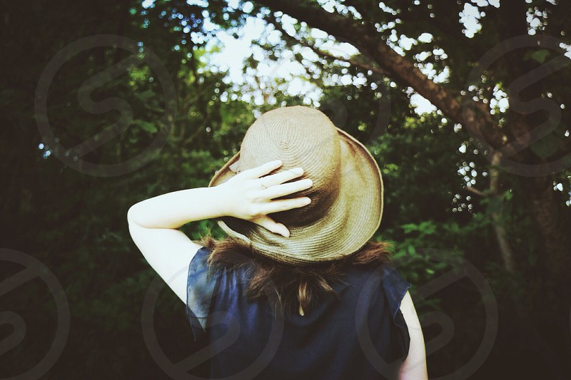 woman in black shirt holding her hat looking at the tree photo