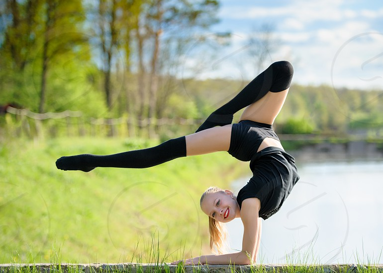 Flexible gymnast girl showing elegant handstand on background of defocused nature scene with wood and water photo
