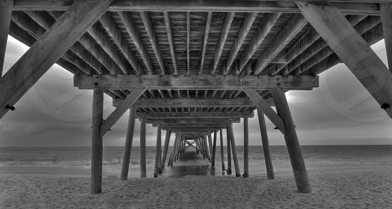 Underside of the wooden pier in HDR with a 3d effect showing the details of the wooden structure.  photo