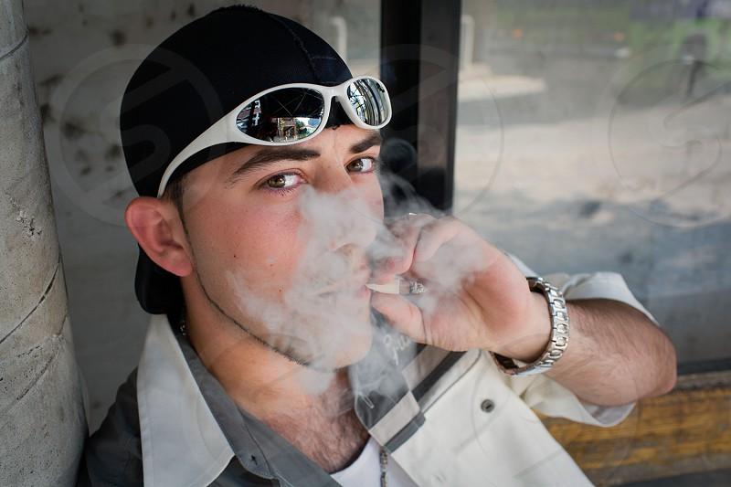 man smoking at bus stop photo